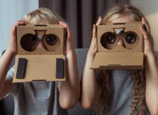 Auf dem Bild sind zwei Kinder zu sehen, die durch eine VR-Pappbrille (Cardboard) schauen (Bild: D-Keine/ E+ via Getty Images)