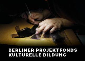 In einer Dunkelkammer kratzt eine Person mit einem Stift in der einen Hand etwas in Foto-Negative hinein. Die andere Hand fixiert die Negative auf einem Tisch.