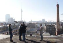 Im Vordergrund dreht eine 5-köpfige Gruppe auf einem Dach einen Film. Links hält eine Person ein großes Mikro, eine andere Person rechts einen Reflektor, in der Mitte stehen zwei Personen hinter und eine vor der Kamera. Im Hintergrund befindet sich die Stadtsilhouette Berlins einschließlich des Fernsehturms an einem sonnigen, wolkenlosen Tag.
