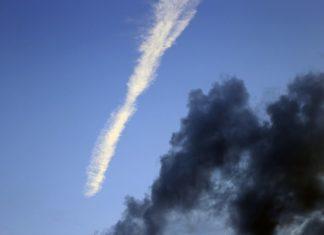 Foto, Kondensstreifen und dunkle Wolken vor klarem Himmel