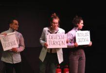 """Schauspieler*innen aus """"Unterscheidet euch!"""" auf der Bühne halten Schilder in der Hand, auf der unterschiedliche Begriffe zur Sortierung bzw. Zuordnung stehen."""